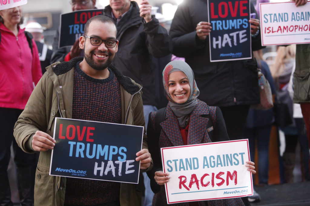 """NEW YORK, NY - MARCH 16: Ben O'Keefe and Iram Ali of MoveOn.org Political Action stand outside the studios of ""Good Morning America"" to broadcast messages of love, dignity, and equality and stand up against the hate, racism, and incitement of violence that the group says has become a hallmark of Donald Trump's presidential campaign in New York City on Wednesday, March 16, 2016 in New York City. (Photo by Thos Robinson/Getty Images for MoveOn.org Political Action)"""